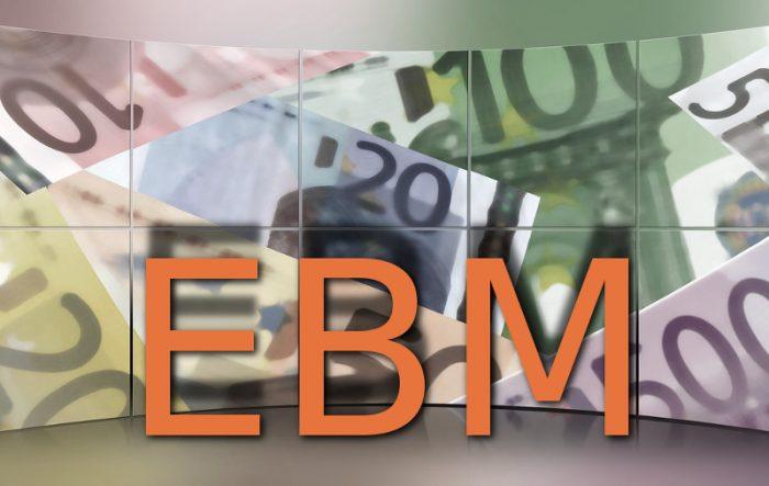 """""""EBM"""" als stehende orange Buchstaben vor einer Wand aus Euro-Scheinen"""