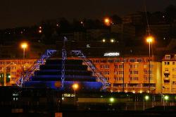 Blick über den Platz. Abendlich angestrahlte Gebäude. Le Méridien im Hintergrund