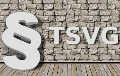"""Paragraphenzeichen und """"TSVG"""" mit Schattenwurf vor dem Hintergrund einer grauen Wand"""