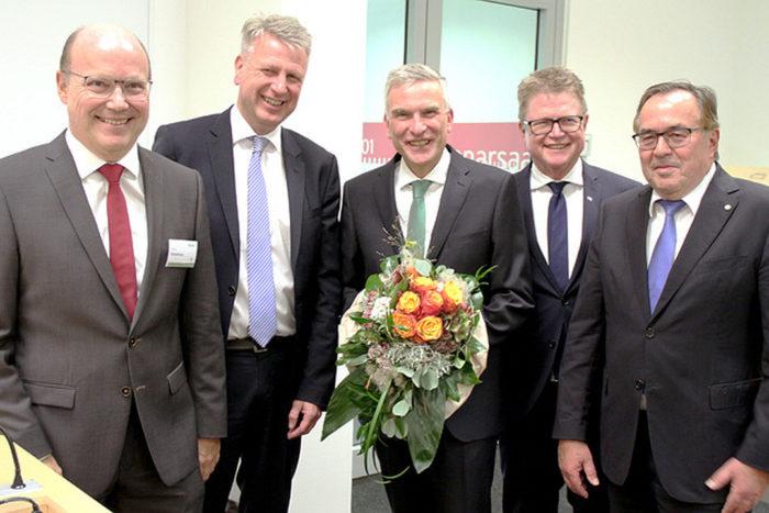 5 Herren im Anzug. Der mittlere trägt einen Blumenstrauß