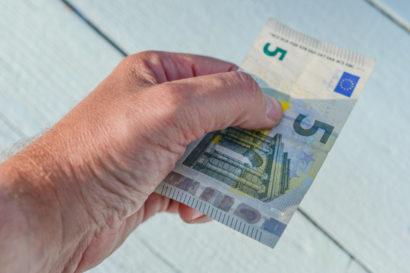 Eine Männerhand reicht einen 5-Euro-Schein